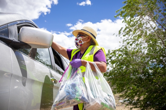 Marlene Thomas hands out homemade masks while Navajo families wait in line to receive food, water, and other supplies in Counselor on the Navajo Nation Reservation, New Mexico, on May 27.