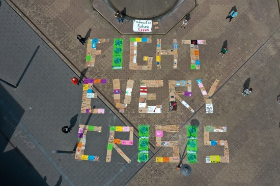 """Demonstrators of the Fridays for Future environmental movement practice social distancing as they stand next to placards arranged to form the words """"Fight Every Crisis"""" in front of the city hall in Essen, Germany, on April 24."""