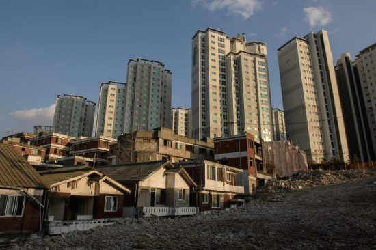 Abandoned houses sit near new high-rise apartments, following evictions prior to redevelopment, in the Ahyeon district of Seoul on Dec. 18, 2018.