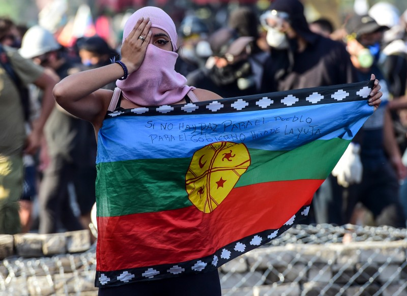 A Chilean demonstrator holds a Mapuche Indigenous flag
