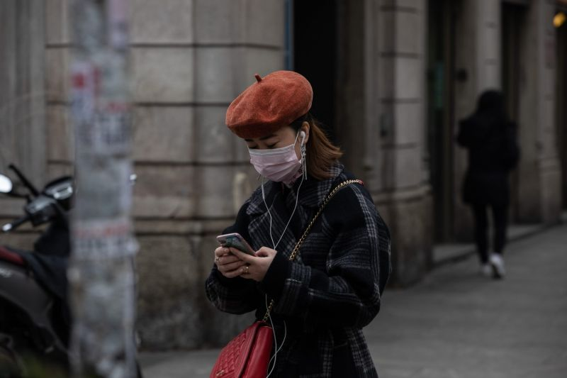 A woman uses her smartphone as she stands in Milan's Chinatown in the Paolo Sarpi district on Feb. 25.