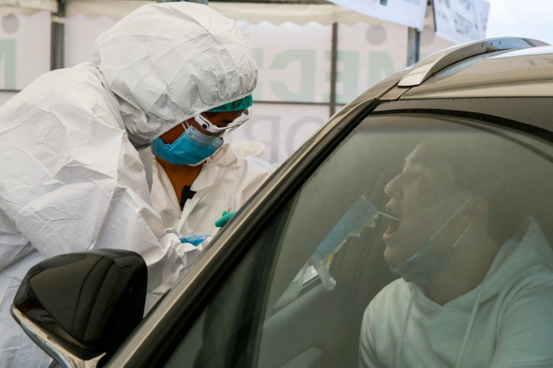 A health care worker gives a COVID-19 test to a medical staff near Halyk Arena in Almaty on July 5, as Kazakhstan imposed a second round of nationwide restrictions to counter a huge surge in coronavirus cases.