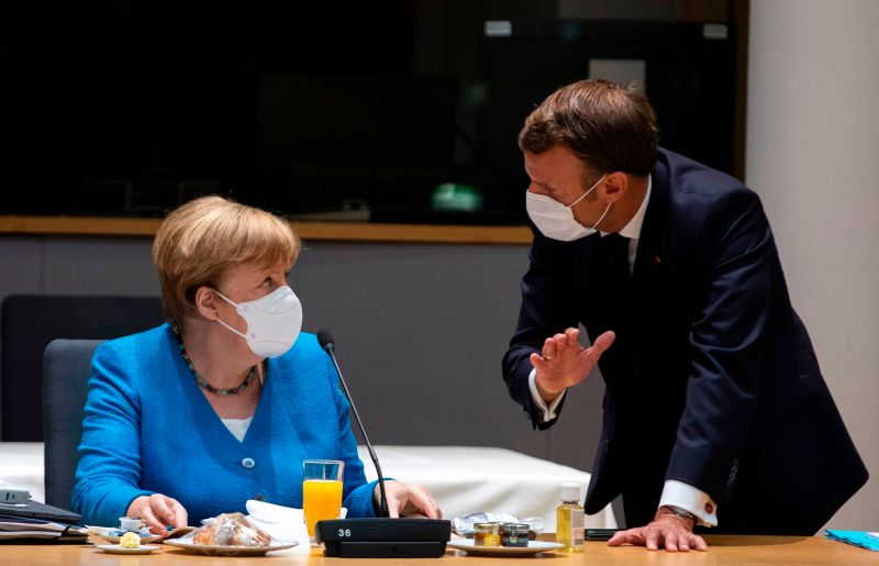 German Chancellor Angela Merkel talks with French President Emmanuel Macron prior to the start of an EU summit at the European Council building in Brussels on July 18.