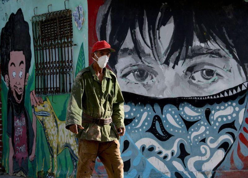 A man wearing a face mask walks along a street of Havana on July 29.
