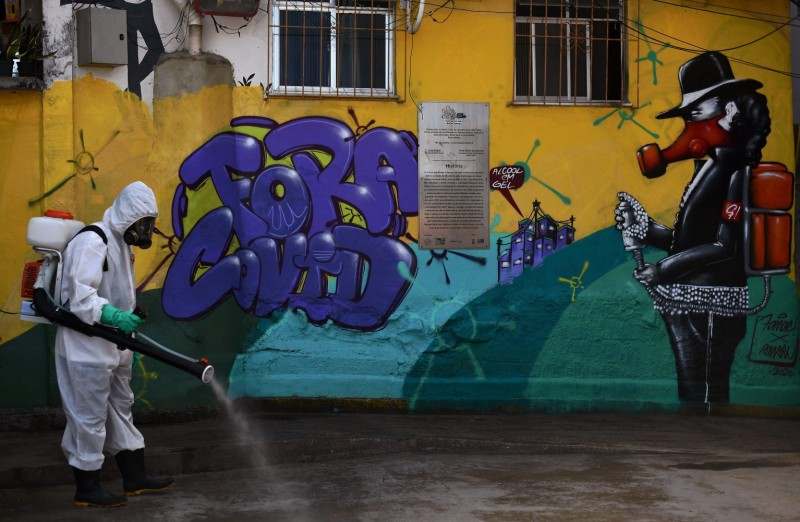 A volunteer disinfects an area inside Santa Marta Favela in Brazil