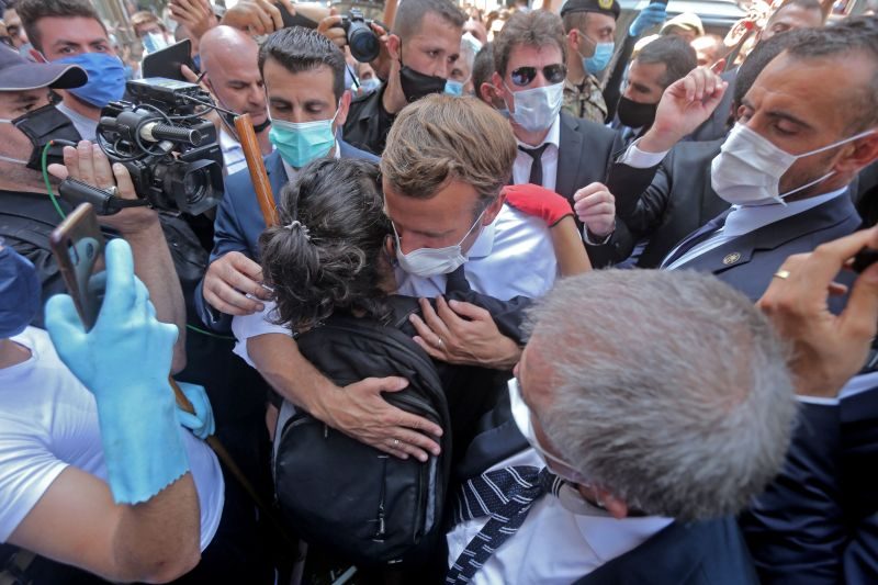 A Lebanese youth hugs French President Emmanuel Macron during a visit to the Gemmayzeh neighborhood of Beirut, which has suffered extensive damage due to a massive explosion in the Lebanese capital, on Aug. 6, 2020.