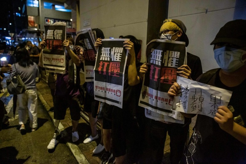 Jimmy Lai supporters hold copies of the Apple Daily newspaper