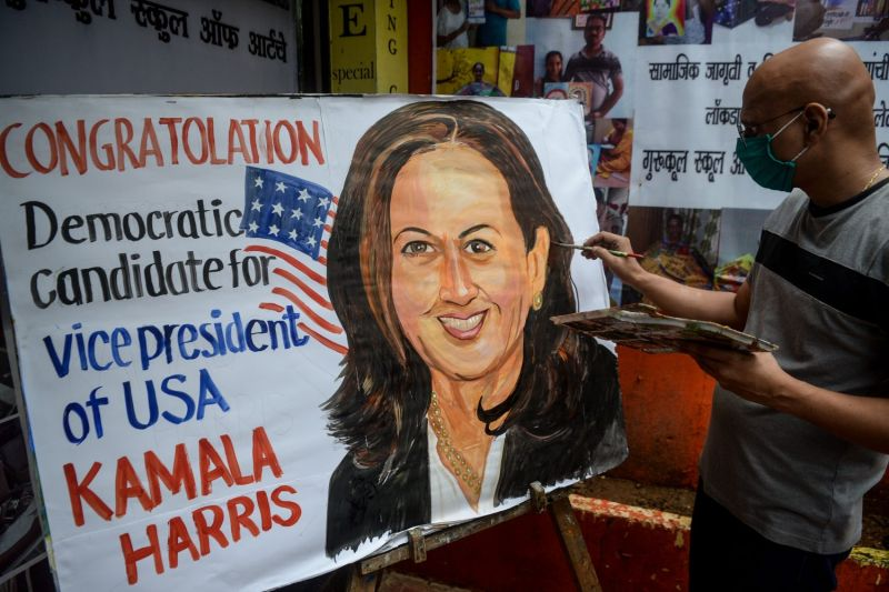 An art enthusiast paints  the face of U.S. vice presidential candidate Kamala Harris outside a drawing school in Mumbai on Aug. 13.