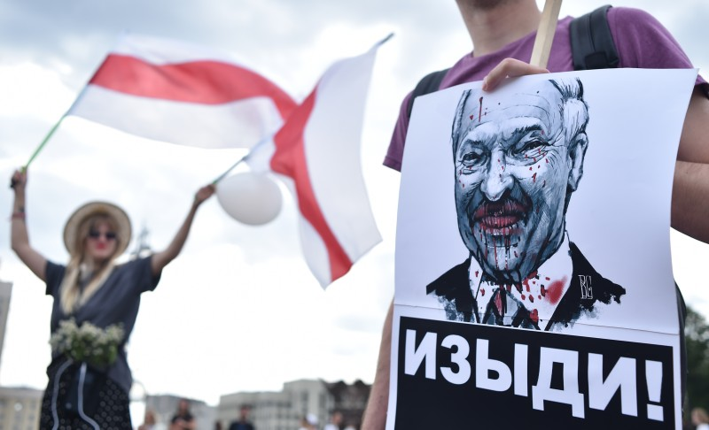 "A man holds a picture of Belarus President Alexander Lukashenko reading ""Go away!"" during a protest rally against police violence during recent rallies of opposition supporters."
