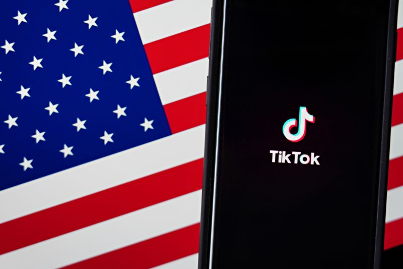In this photo illustration, a mobile phone featuring the TikTok app is displayed next to the American flag.