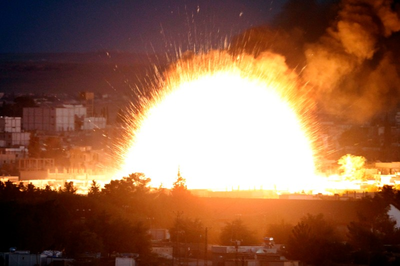 An explosion rocks Syrian city of Kobani during a reported suicide car bomb attack by the militants of Islamic State (ISIS) group on a People's Protection Unit (YPG) position in the city center of Kobani, as seen from the outskirts of Suruc, on the Turkey-Syria border, Oct. 20, 2014.