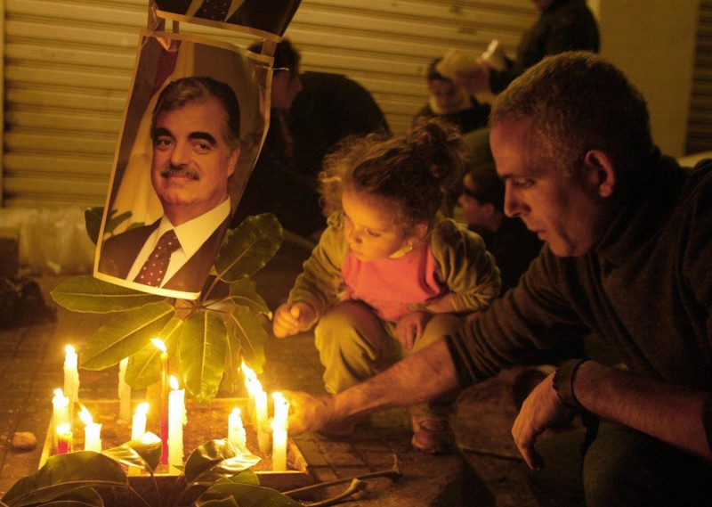 A Lebanese father and his daughter light a candle outside the mansion of assassinated former Lebanese premier Rafik Hariri
