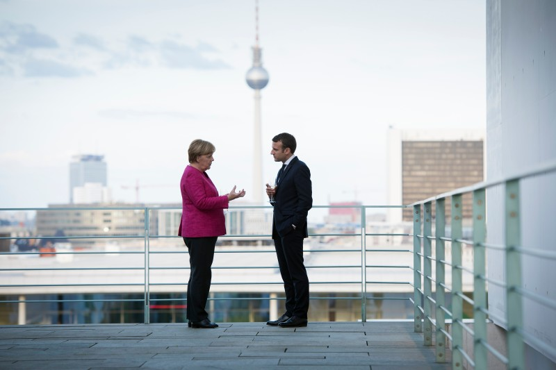 German Chancellor Angela Merkel talks with newly-elected French President Emmanuel Macron on the terrace, with a view of the television tower in the background during his visit to the chancellor's office on May 15, 2017 in Berlin, Germany.