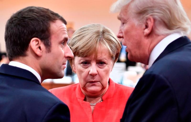 German Chancellor Angela Merkel speaks with U.S. President Donald Trump and French President Emmanuel Macron.