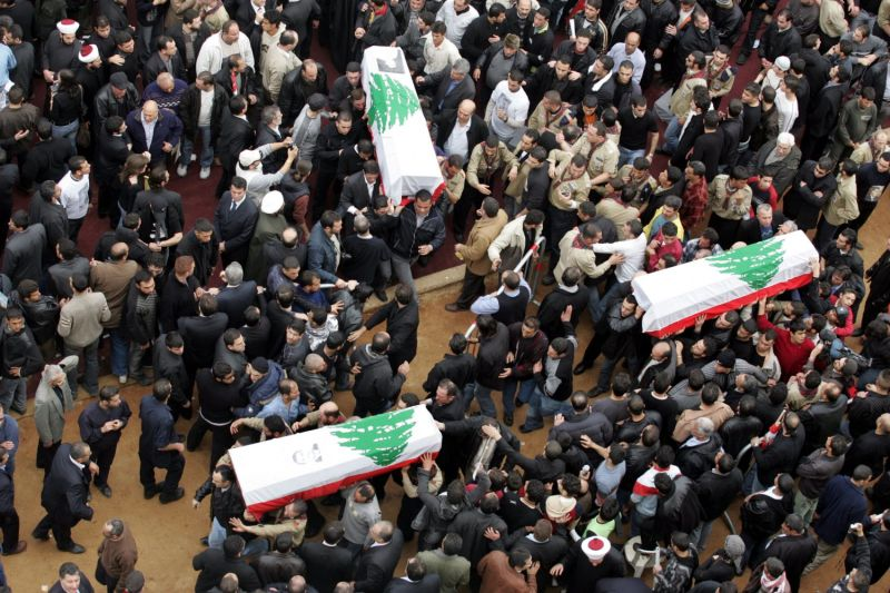 Coffins of three of the seven bodyguards of Lebanon's murdered prime minister Rafiq Hariri are carried through the crowd during a mass funeral in central Beirut  on 16 February 2005. Hariri and his bodyguards were buried after his coffin was caught in a crush of frenzied mourners outside a Beirut mosque. AFP PHOTO/JOSEPH BARRAK.