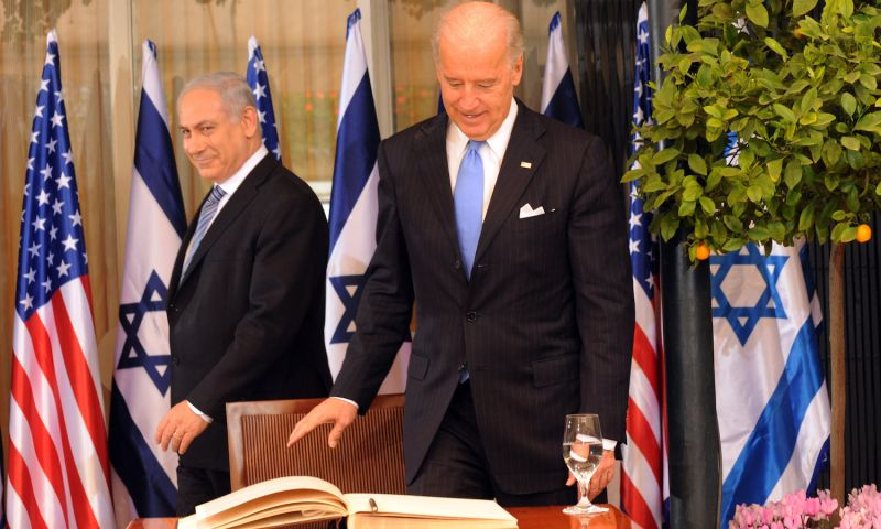 Israeli Prime Minister Benjamin Netanyahu walks past then-U.S. Vice President Joe Biden as he prepares to sign the guest book at the prime minister's residence in Jerusalem on March 9, 2010.
