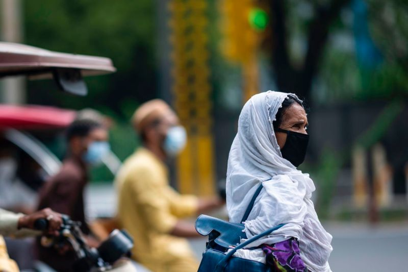 A woman waits to cross a street in New Delhi on Aug. 1.