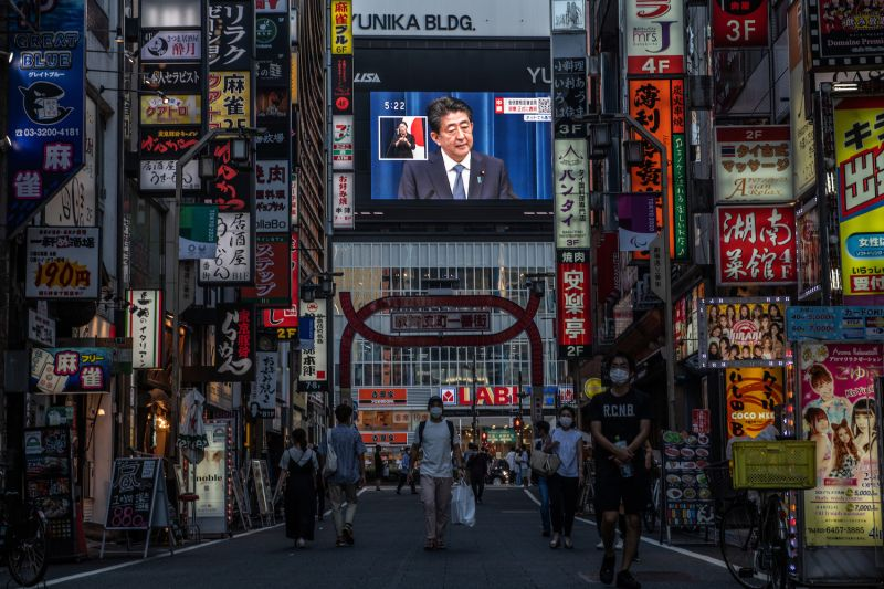 People pass by as Japan's Prime Minister, Shinzo Abe, is displayed on a giant television screen during a press conference in Tokyo on Aug. 28.