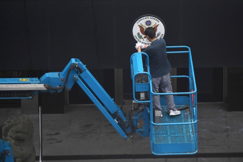 A worker removes the sign at the entrance to the U.S. consulate in Chengdu, in Sichuan province, China, on July 25.