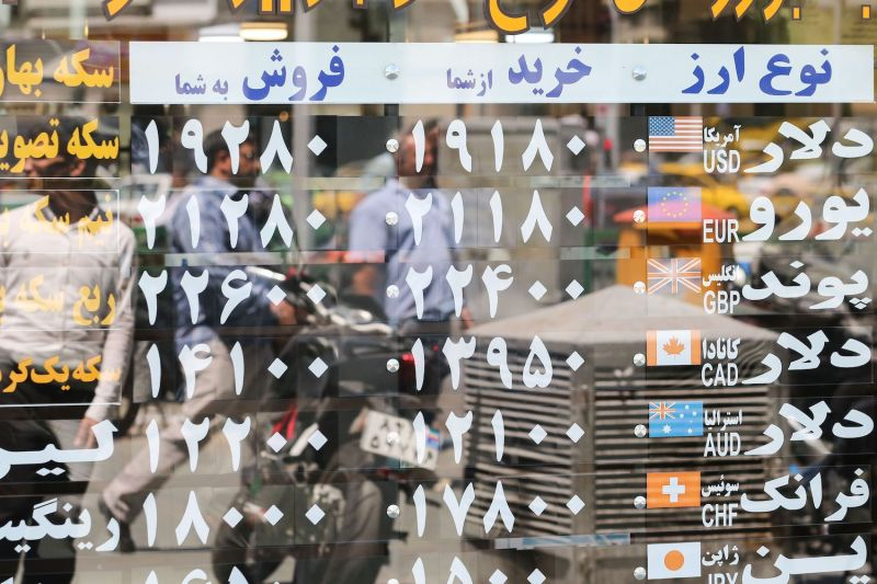 Pedestrians are reflected in a window displaying currency exchange rates in Tehran on June 22.