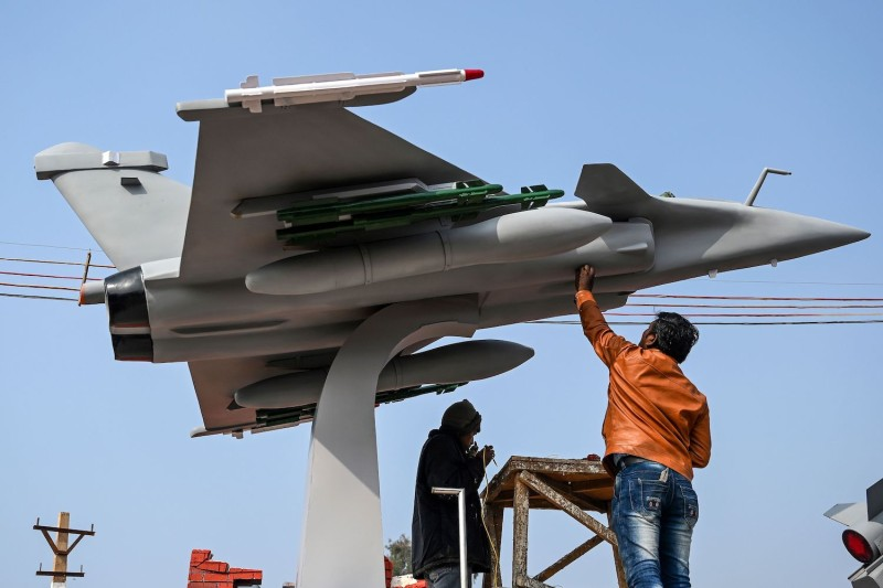 Workers put final touches on a model of a Rafale fighter jet ahead of the Republic Day parade in New Delhi on Jan 22.