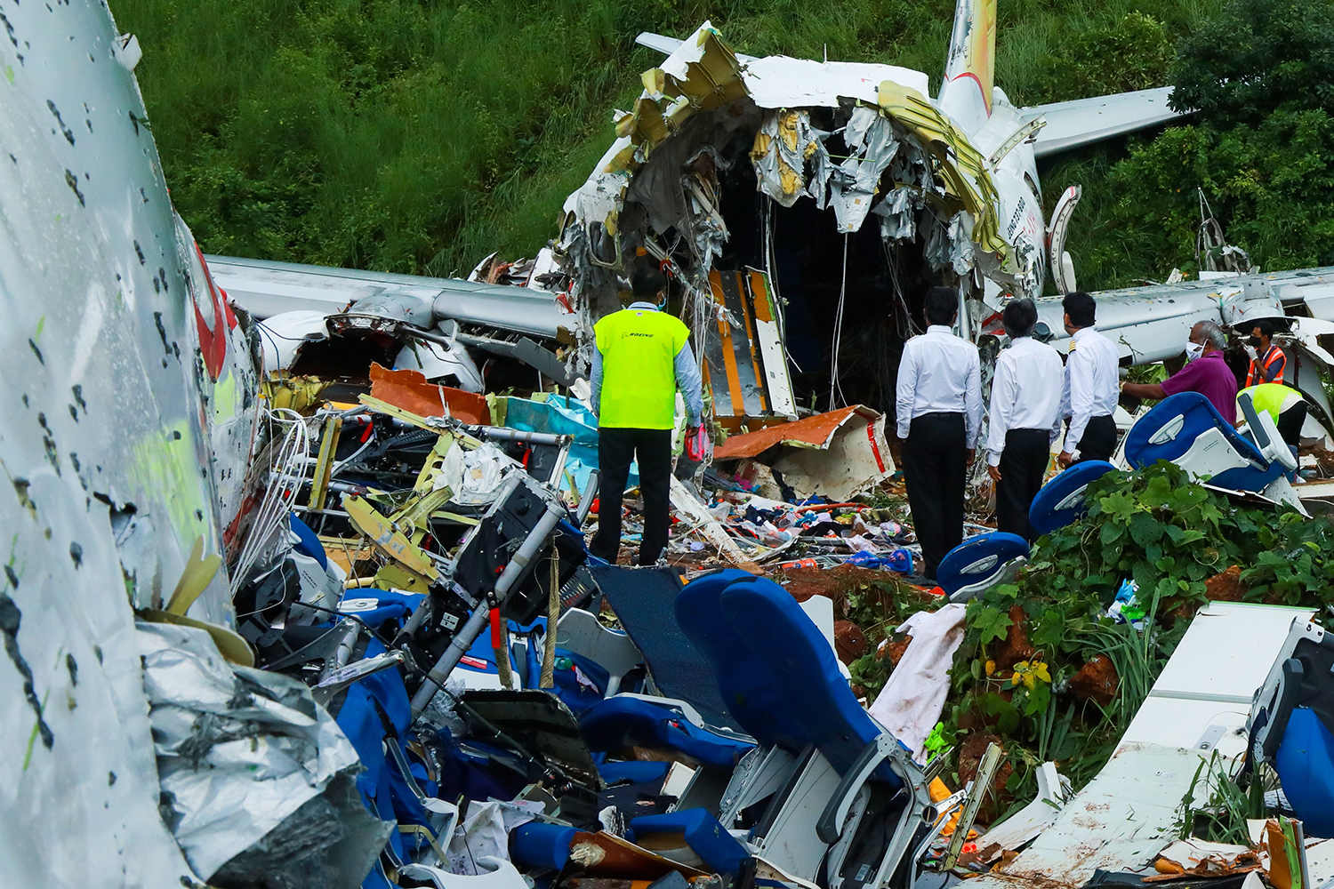 Officials inspect the wreckage of an Air India Express jet at Calicut International Airport in Karipur, India, on Aug. 8. Fierce rain and winds lashed a plane carrying 190 people before it crash-landed and tore in two, killing 18 people. ARUNCHANDRA BOSE/AFP via Getty Images