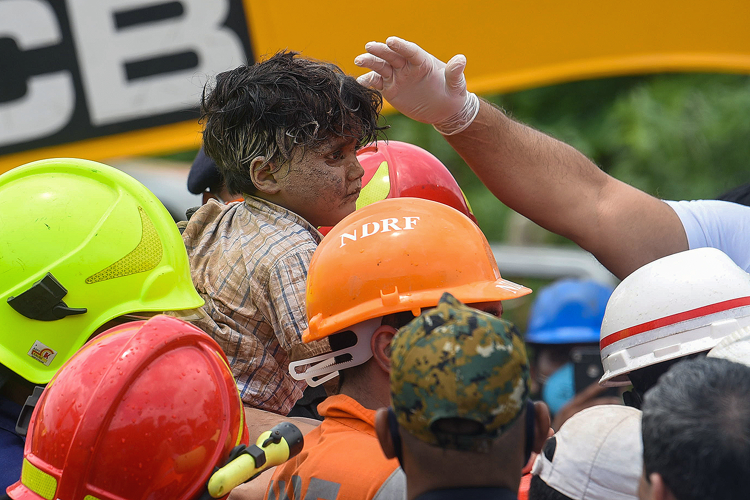 Rescue workers carry a 4-year-old boy who was pulled from the rubble of a collapsed five-story apartment building in Mahad, India, on Aug. 25. MANOEJ PAATEEL/AFP via Getty Images