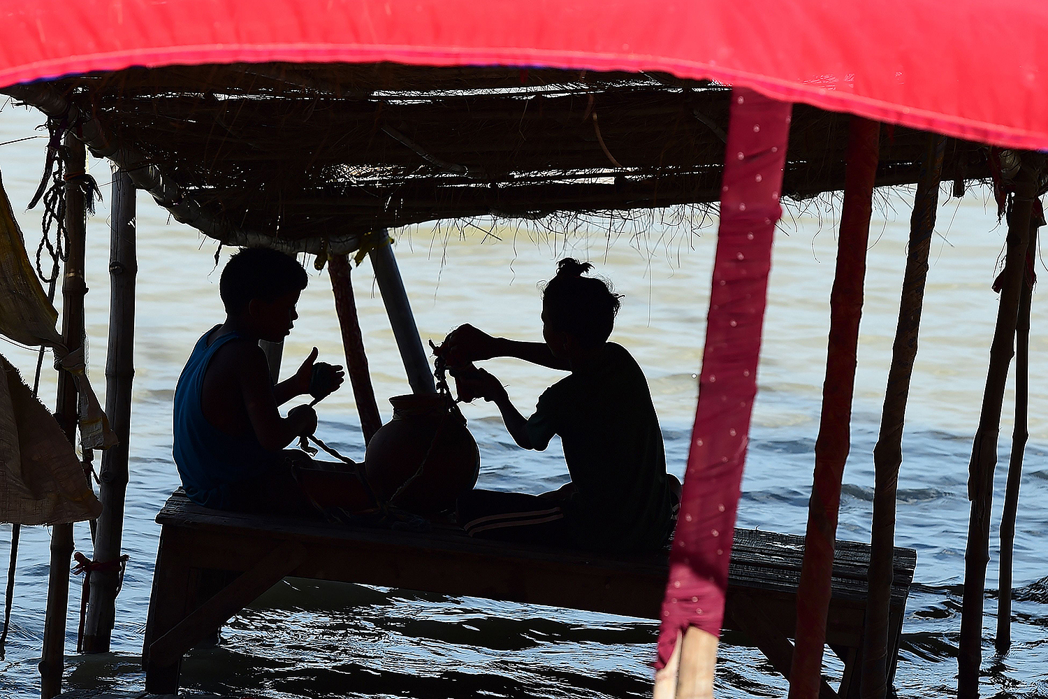 Children sit under the shade of a partially submerged hut as the water level of the Ganges and Yamuna rivers rises in Allahabad, India, on Aug. 25. SANJAY KANOJIA/AFP via Getty Images