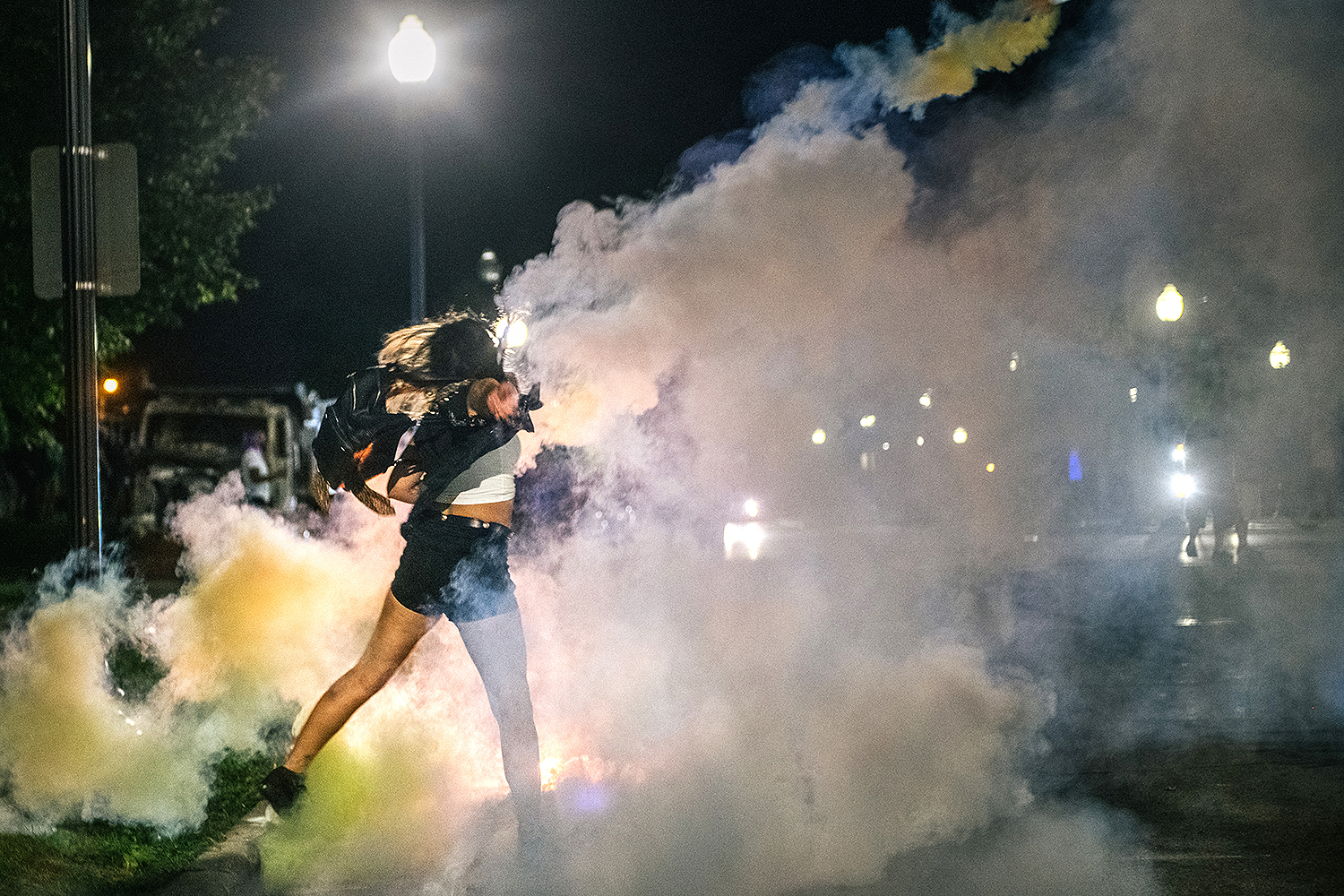 A demonstrator throws back a can of tear gas in Kenosha, Wisconsin, on Aug. 25 during protests two days after Jacob Blake, a Black man, was shot multiple times in the back by police. Brandon Bell/Getty Images