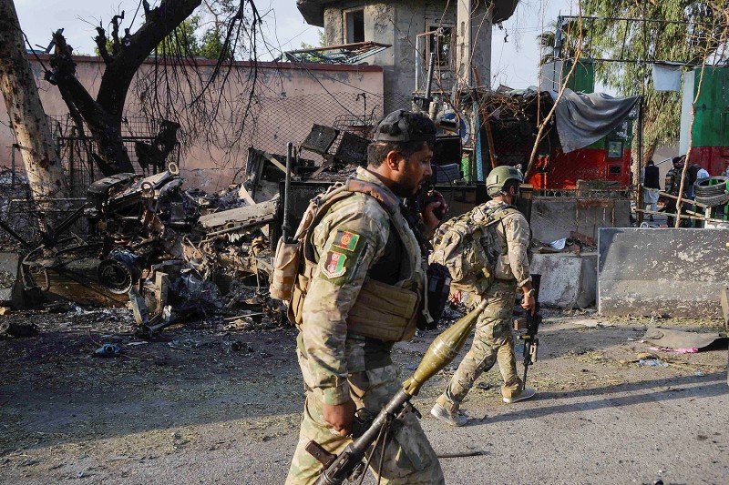 Afghan soldiers walk past debris near the main prison entrance after a raid in Jalalabad on Aug. 3. Dozens were killed when gunmen attacked the prison in eastern Afghanistan; the Islamic State claimed responsibility.