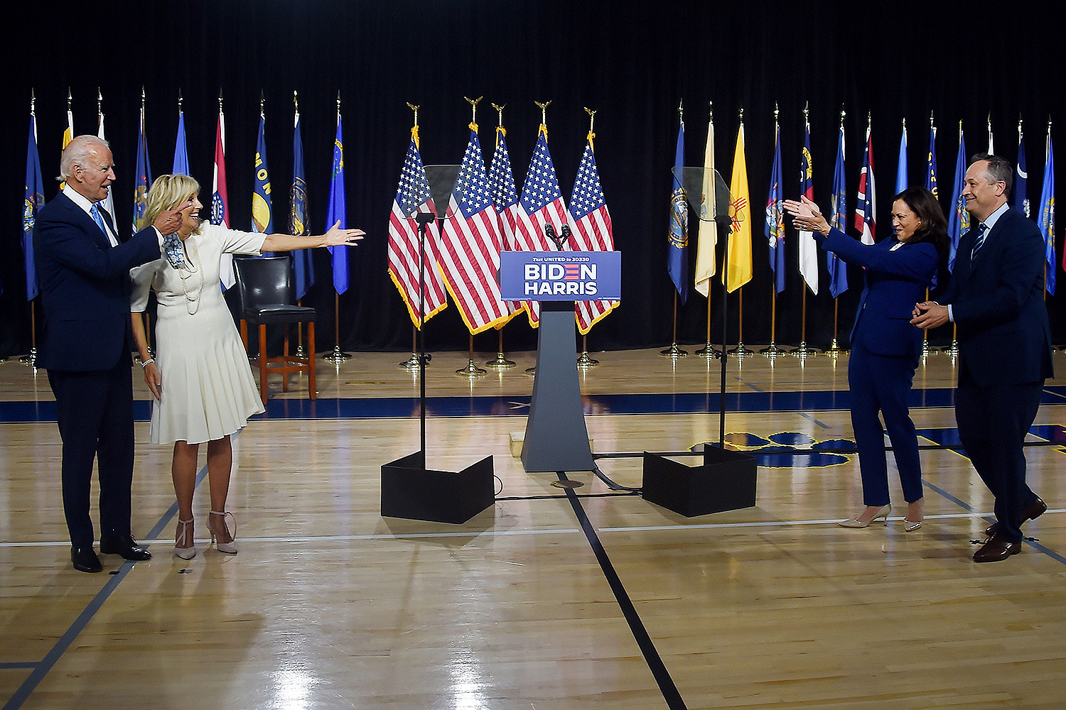 Democratic presidential nominee Joe Biden (left) and his wife, Jill Biden, wave to vice presidential running mate Kamala Harris and her husband, Douglas Emhoff, after their first press conference together in Wilmington, Delaware, on Aug. 12. OLIVIER DOULIERY/AFP via Getty Images