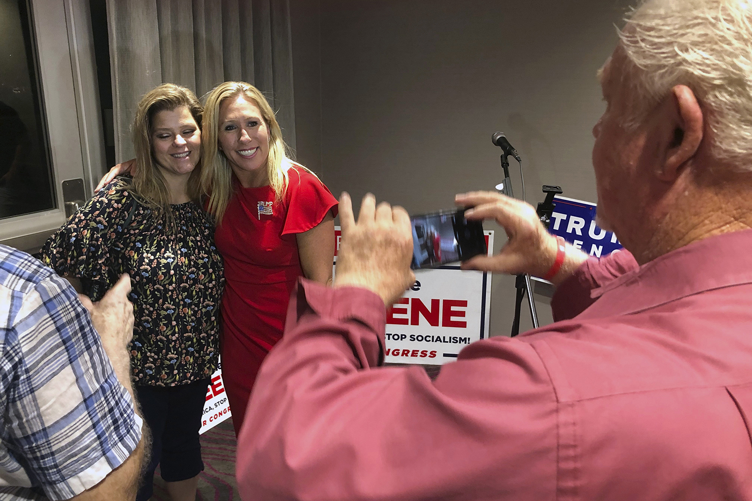 Supporters take photos with Marjorie Taylor Greene (in red) in Rome, Georgia, on Aug. 11. Greene, a QAnon supporter, won the GOP nomination for northwest Georgia's 14th U.S. Congressional District.