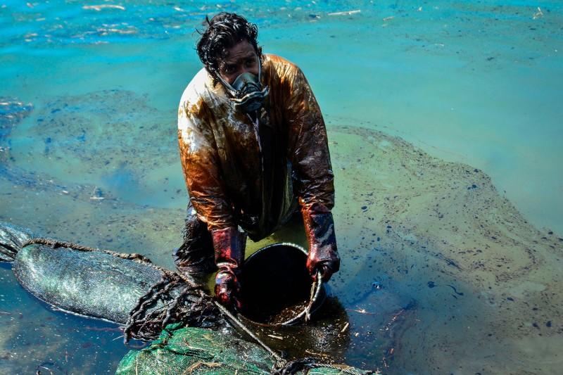 A man scoops leaked oil from the vessel MV Wakashio near Blue Bay Marine Park off the coast of southeast Mauritius on Aug. 8. The ship hit a coral reef off the Indian Ocean island and ran aground two weeks prior, spilling about 1,000 tons of oil. JEAN AURELIO PRUDENCE/L'Express Maurice/AFP via Getty Images