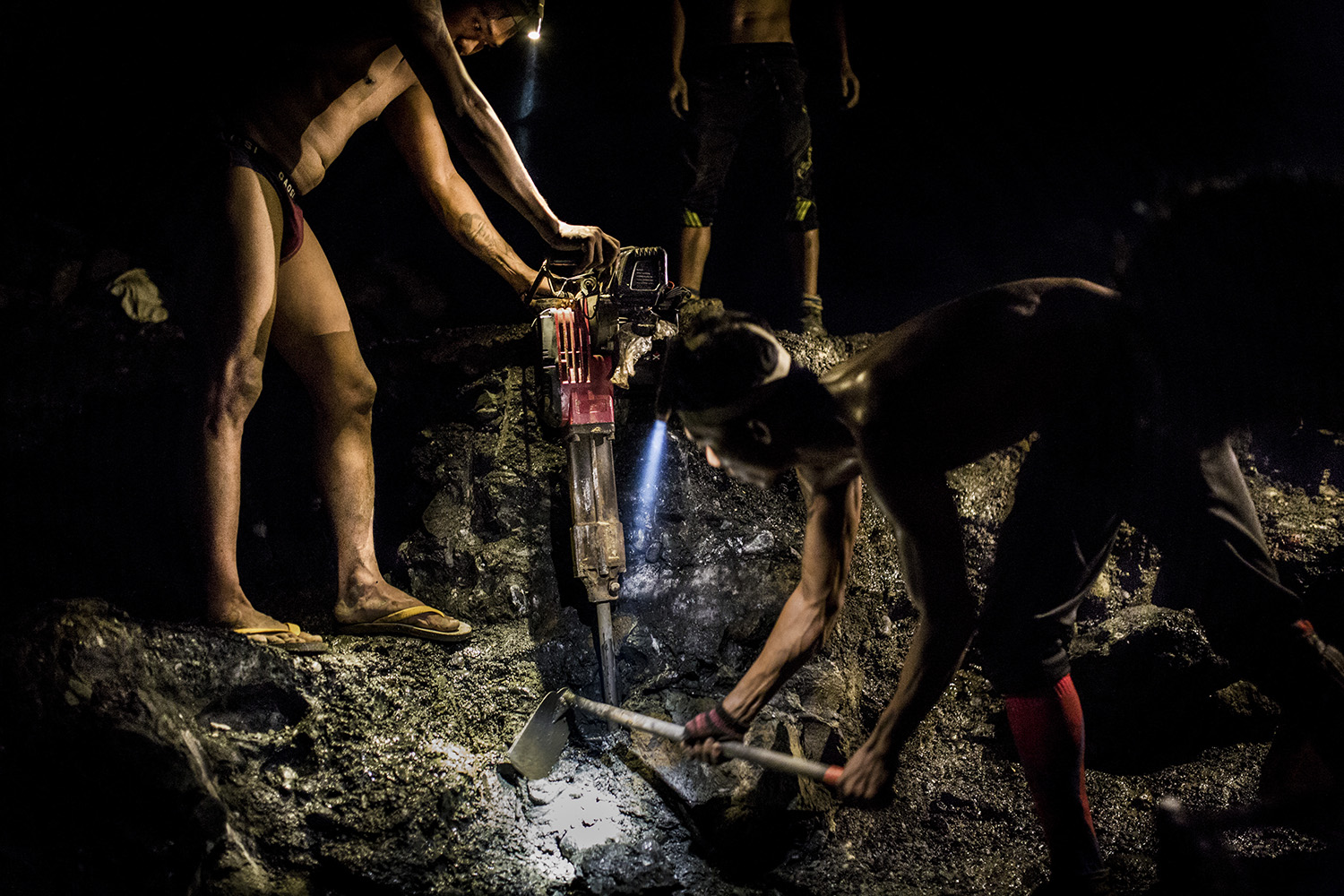 Miners use jackhammers and headlamps to search for jade at night in Hpakant on Aug. 15, 2018.