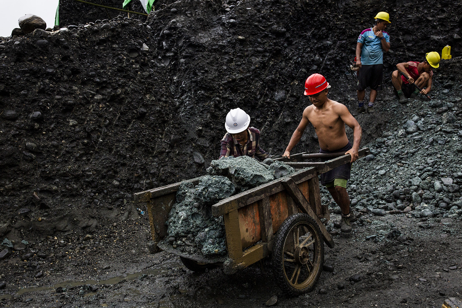 A team of freelance miners cart away stones from a jade mine in Hpakant on July 17.