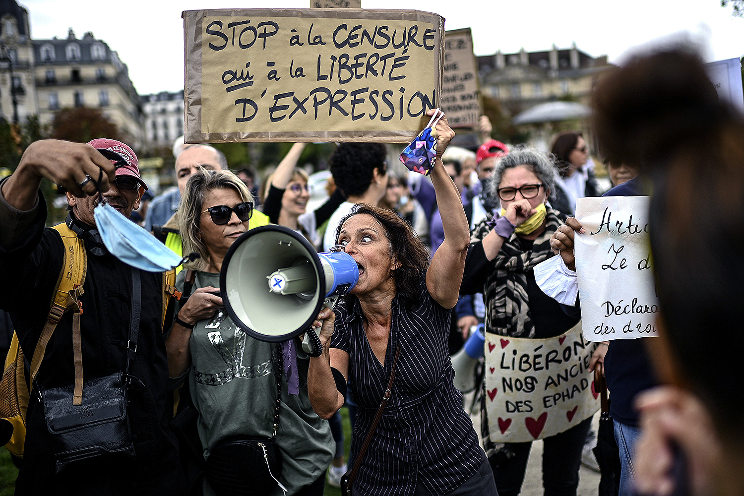 "A woman holding a placard reading ""Stop Censorship—Yes to the Freedom of Expression"" shouts into a megaphone during a protest against the mandatory wearing of face masks on the Place de La Nation in Paris on Aug. 29. Masks were made mandatory outdoors citywide the day before to fight the rising coronavirus infections. CHRISTOPHE ARCHAMBAULT/AFP via Getty Images"