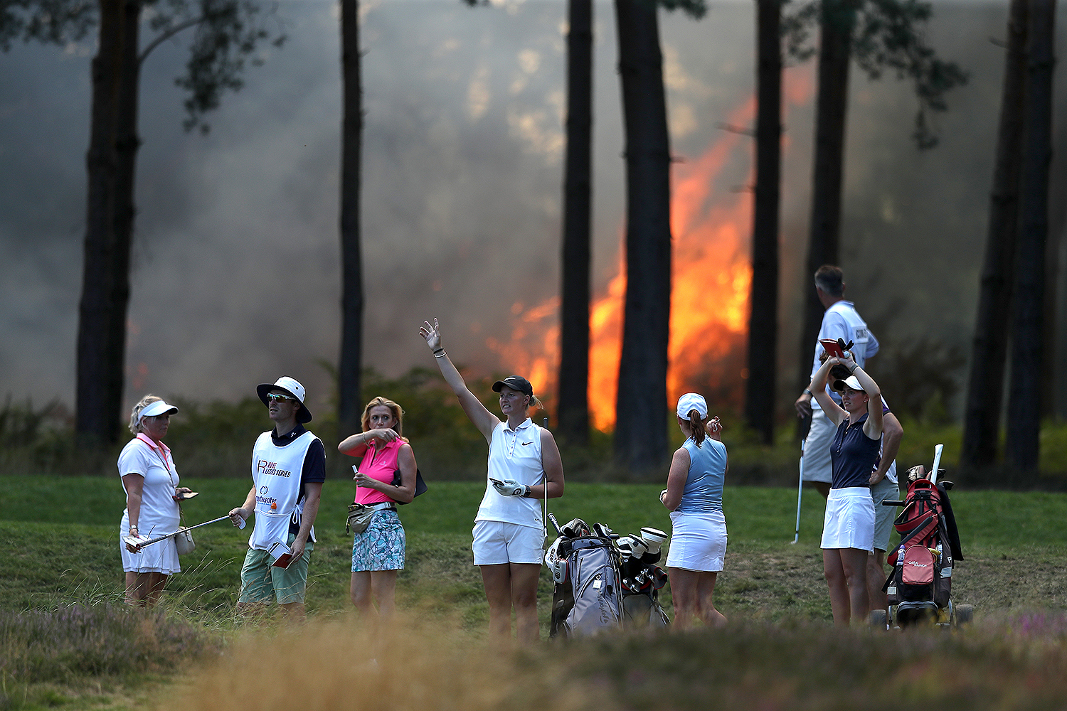 Golfers and their caddies look on as a wildfire nears the 10th hole during the Rose Ladies Series Order of Merit event at Wentworth Golf Club in Virginia Water, England, on Aug. 7. The next day, the final round was canceled because of the wildfires. Naomi Baker/Getty Images