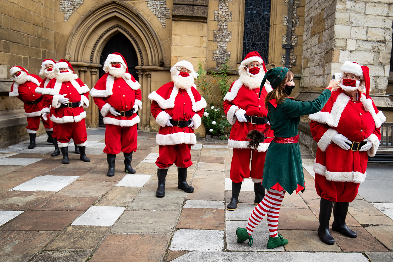 Santas at the Ministry of Fun's Summer School in Southwark Cathedral, London, have their temperature taken Aug. 24. The school aims to create COVID-safe Christmas grottos by teaching Father Christmases how to appear safely in person while maintaining the Christmas magic. Aaron Chown/PA Images via Getty Images