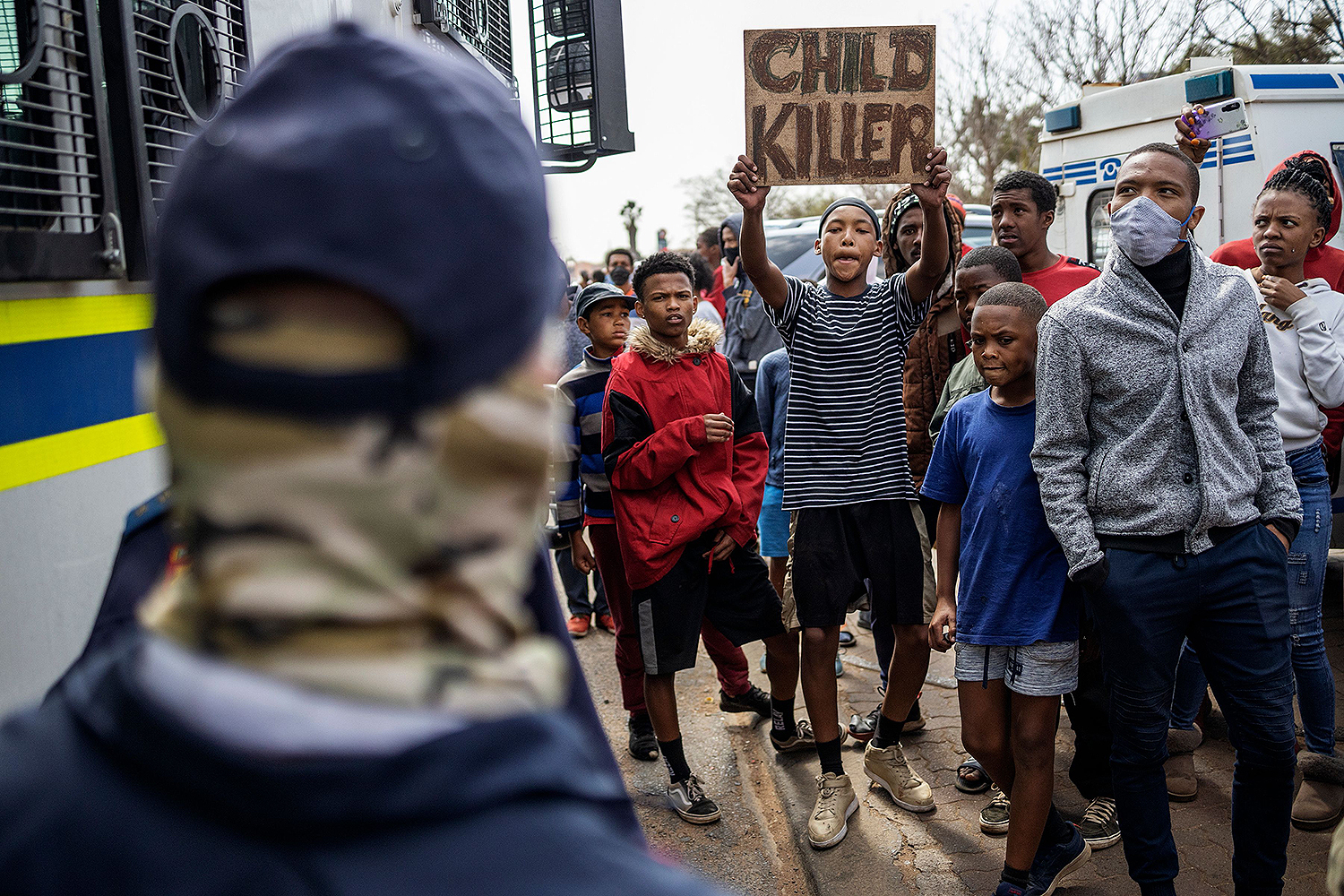"A resident holds up a ""Child Killer"" sign near members of the South African Police Service in Eldorado Park, near Johannesburg, on Aug. 27 during a protest after a 16-year-old boy was shot and killed by police. MICHELE SPATARI/AFP via Getty Images"
