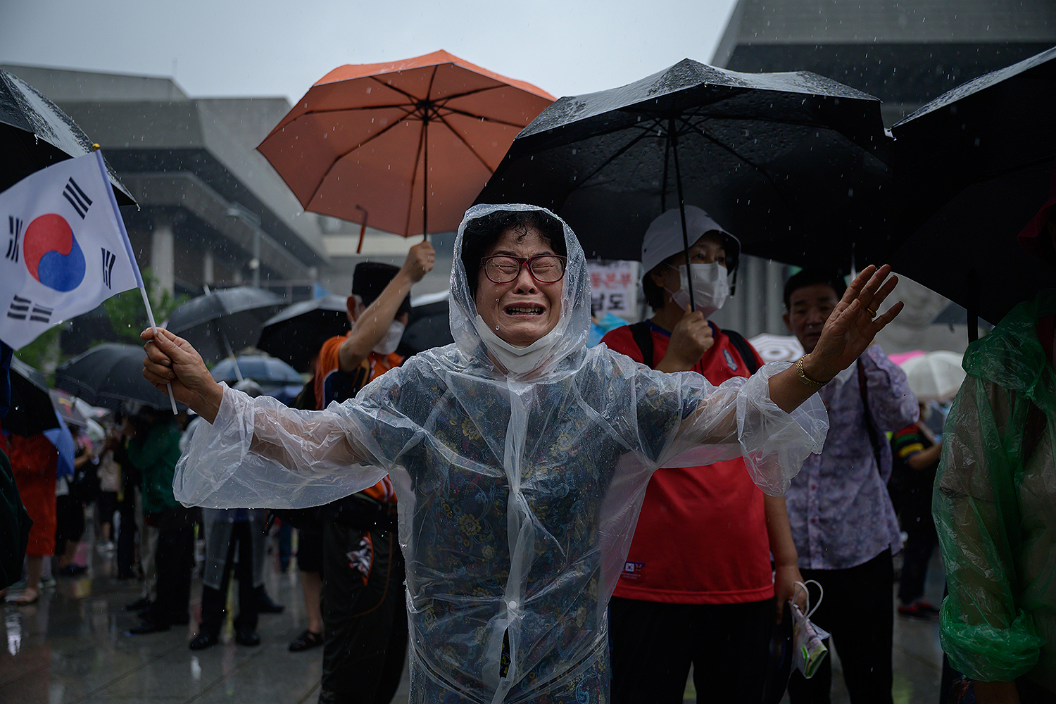 A woman weeps as members of conservative right-wing groups wave flags and shout slogans during an anti-government rally in the central Gwanghwamun area of Seoul on Aug. 15. ED JONES/AFP via Getty Images