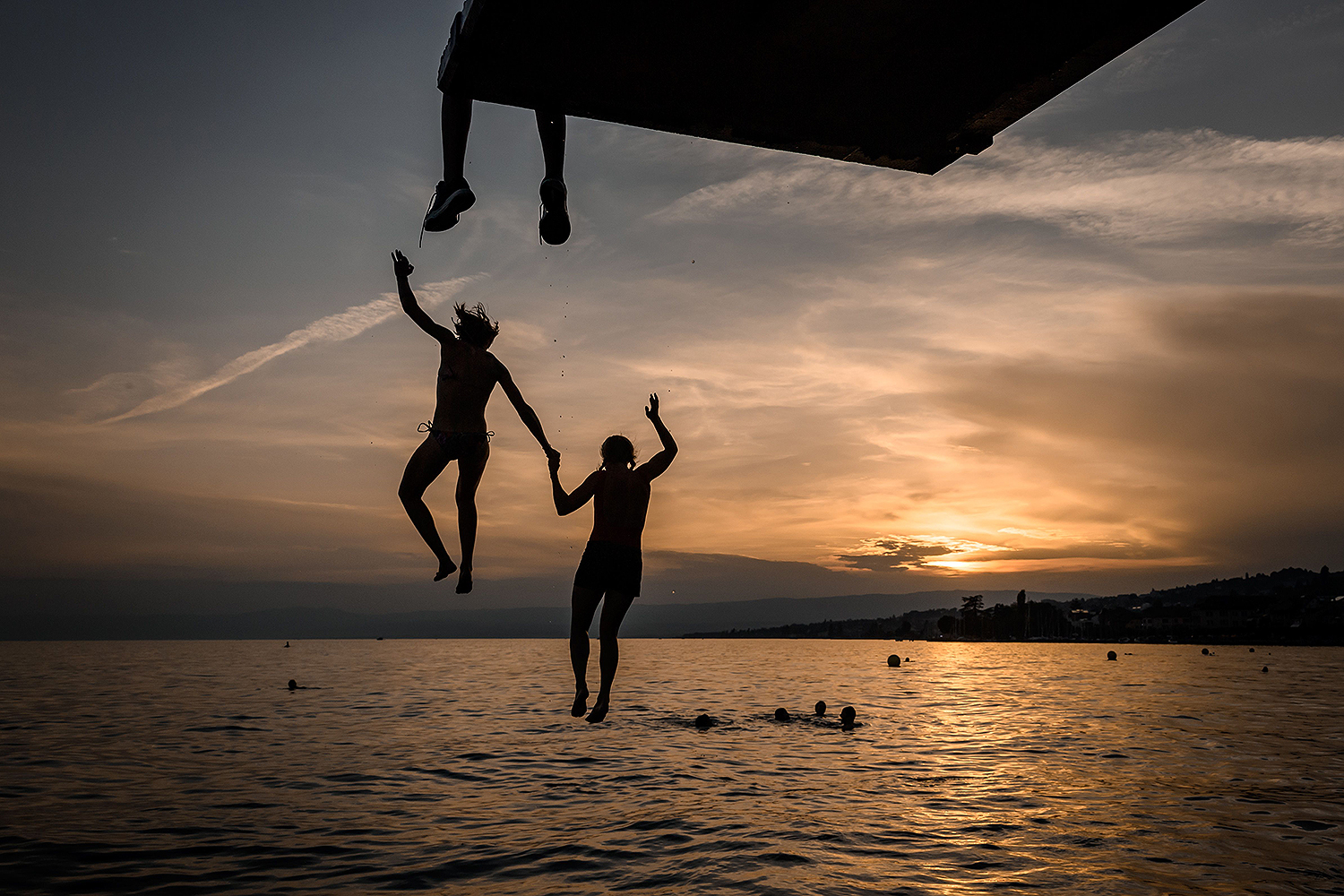 A couple jump from a diving platform in Lake Geneva near the village of Lutry, Switzerland, at sunset Aug. 9 as a heatwave swept across Europe. FABRICE COFFRINI/AFP via Getty Images