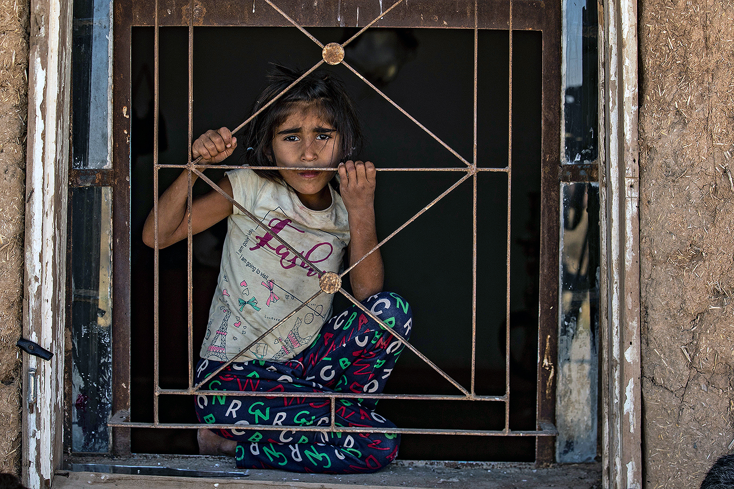 A Syrian girl looks out from a house in the countryside of Qamishli, in Syria's Kurdish-controlled northeastern Hasakeh province, on Aug. 17. DELIL SOULEIMAN/AFP via Getty Images