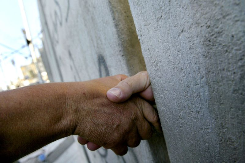 Hassan Ayad sticks his hand through concrete blocks as he is congratulated by a friend on his recent engagement while the two Palestinian men stand on opposite sides of Israel's security wall in East Jerusalem on September 23, 2003.
