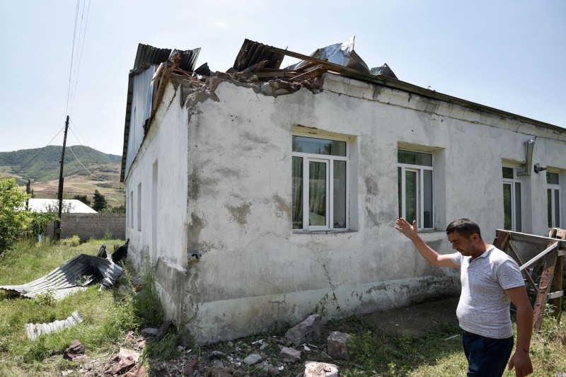 A man gestures as he shows the roof of a kindergarten which suffered of bombing attacks on July 18 in the village of Aygepar, recently damaged by shelling during armed clashes on the Armenian-Azerbaijani border.