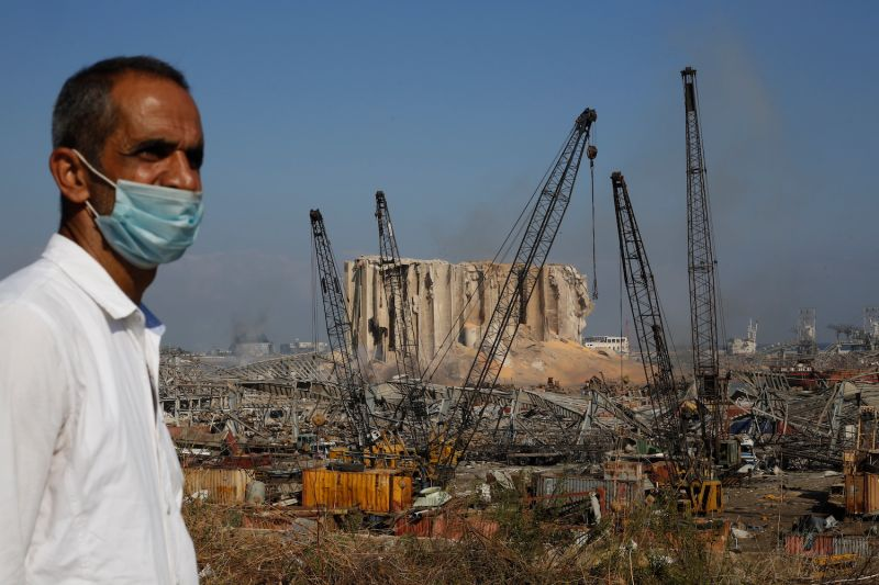 A man in a mask stands before smoldering buildings near Beirut's port on Aug. 5.