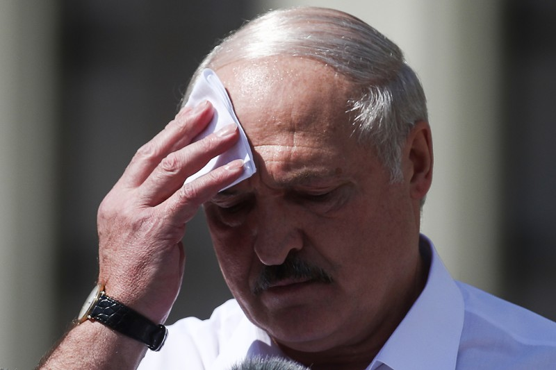 President of Belarus Alexandr Lukashenko wipes his face as he gives a speech during a rally of his supporters in Independence Square in Minsk on Aug. 16.