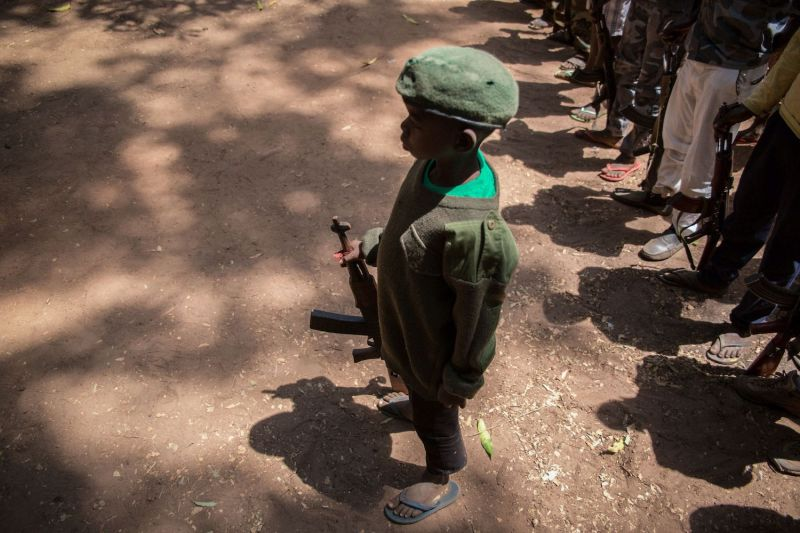 Newly released child soldiers stand with rifles during their release ceremony in Yambio, South Sudan, on February 7, 2018.