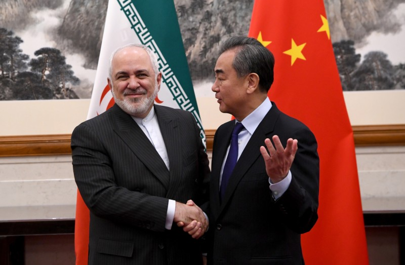 Chinese Foreign Minister Wang Yi shakes hands with Iranian Foreign Minister Mohammad Javad Zarif during a meeting.