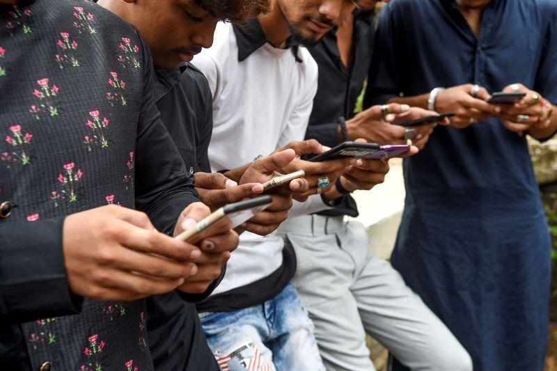 Young men watch videos on TikTok in Mumbai