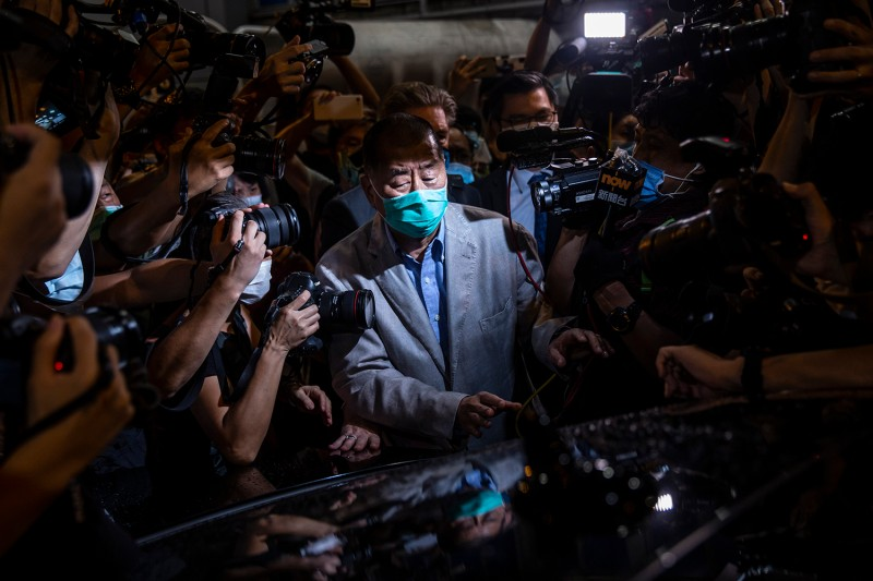 Hong Kong pro-democracy media mogul Jimmy Lai pushes through a media pack after being released on bail in Hong Kong on Aug. 12.
